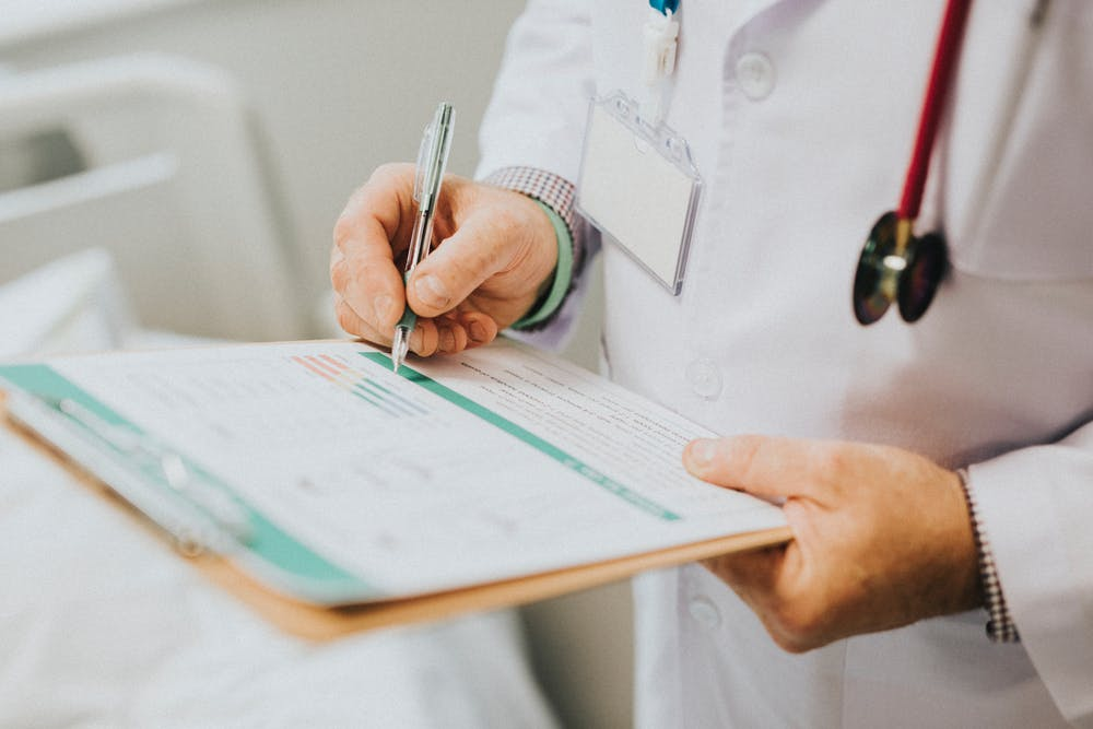 doctor writing in a medical certificate